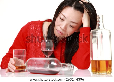 Japanese woman in depression is drinking alcohol - stock photo