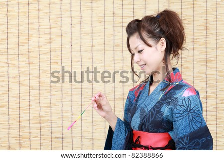 Japanese woman in traditional clothes of Kimono, holding sparkler