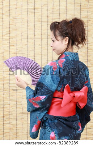 Japanese woman in traditional clothes of Kimono with a japanese fan - stock photo