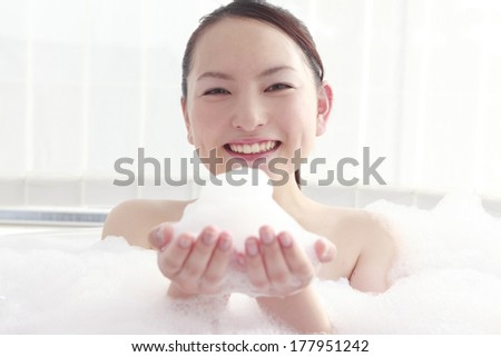 Japanese woman of Japanese businesswoman having the bubbles on hand in the bath