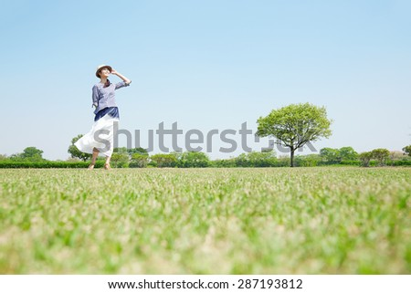 Japanese woman on green field - stock photo
