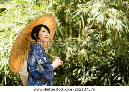 Japanese woman wearing kimono, standing in the park