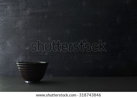 Japanese wooden bowl on the table and black color wooden background - stock photo