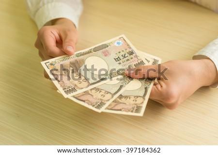 japanese yen with hand - stock photo