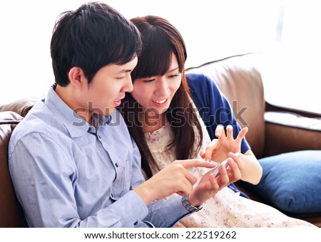Japanese young couple looking a smart phone at home. Happy young couple smiling - stock photo