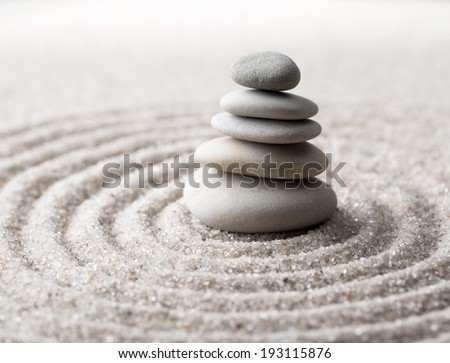 Japanese zen garden meditation for concentration and relaxation. Sand circles in spiral and rocks for harmony and balance in pure simplicity. Macro lens shot. - stock photo