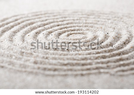 Japanese zen garden meditation for concentration and relaxation. Sand circles in spiral for harmony and balance in pure simplicity. Macro lens shot. - stock photo