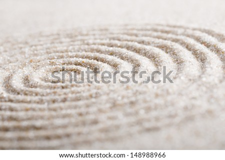 Japanese zen garden meditation stone for concentration and relaxation sand and rock for harmony and balance in pure simplicity - macro lens shot - stock photo
