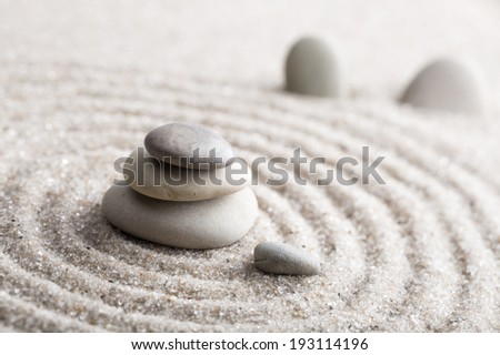 Japanese zen garden meditation stone for concentration and relaxation sand and rock for harmony and balance in pure simplicity - macro lens shot