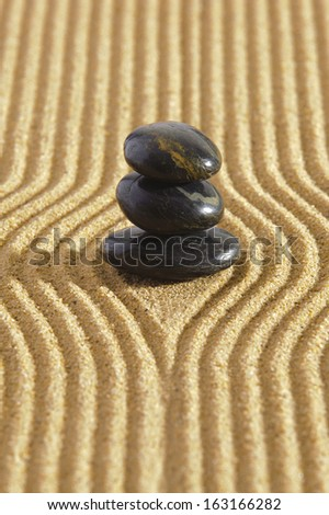 Japanese ZEN garden with stacked stones in raked sand - stock photo