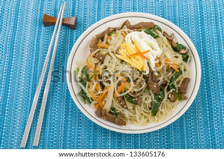 Japchae - Stir fried Korean sweet potato noodles with vegetables, mushrooms and beef garnished with slices of fried egg and sesame seeds.
