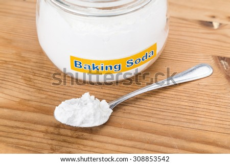 Jar and spoonful of baking soda for multiple holistic usages. - stock photo