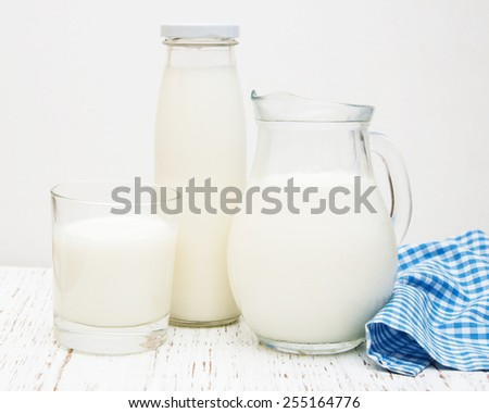 Jar, bottle and glass with fresh milk on a wooden background - stock photo