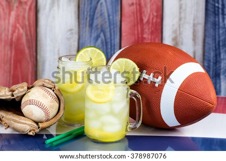 Jar glasses filled with cold lemonade with sporting items.  Faded wooden boards painted red, white and blue in background. Selective focus on upper front jar glass with lime slice.