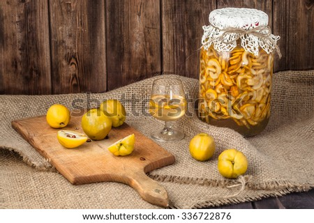Jar of alcohol tincture with cutted quince fruits and glass of drink on a wooden table covered with sackcloth. - stock photo