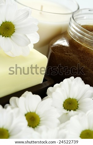 jar of body scrub with soap and flowers - beauty treatment