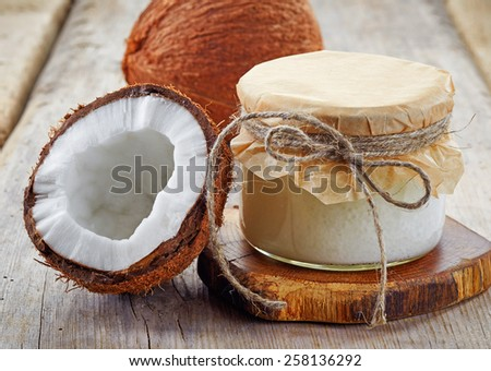 jar of coconut oil and fresh coconuts on wooden table - stock photo