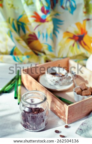 Jar of coffee beans set with a cup of coffee and accessories in colonial style - stock photo