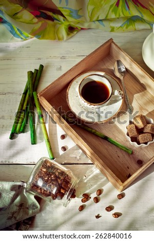 Jar of coffee beans set with a cup of espresso and accessories in colonial style, shallow focus - stock photo