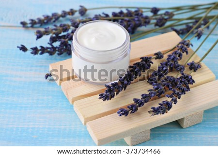 Jar of cream and dried lavender flowers. Herbal beauty treatment. - stock photo