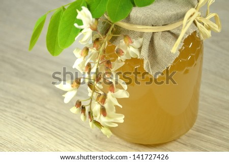 jar of fresh delicious honey with acacia flowers - stock photo