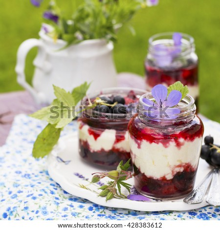 Jar of fresh homemade yogurt with fresh berries ripe for breakfast on a wooden background. The concept of healthy natural foods. selective Focus - stock photo