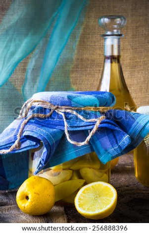 Jar of fruit quince and quince liqueur on a wooden table - stock photo