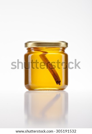 jar of golden honey on a white background with a cinnamon stick inside - stock photo