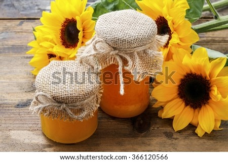 Jar of honey and beautiful sunflowers in the background.