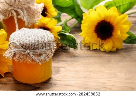 Jar of honey and beautiful sunflowers in the background, copy space