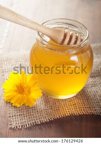 jar of honey and stick on the wooden table