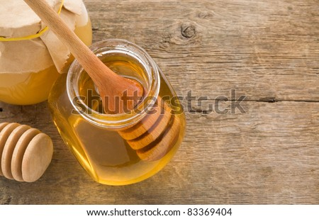 jar of honey and stick on wood background - stock photo