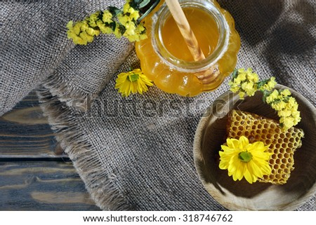 Jar of honey, honeycomb and flowers on sackcloth, top view - stock photo