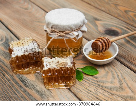 Jar of honey on a old wooden background - stock photo