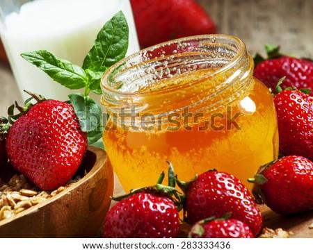 Jar of honey, strawberries, muesli, milk bottle, healthy eating concept, selective focus - stock photo