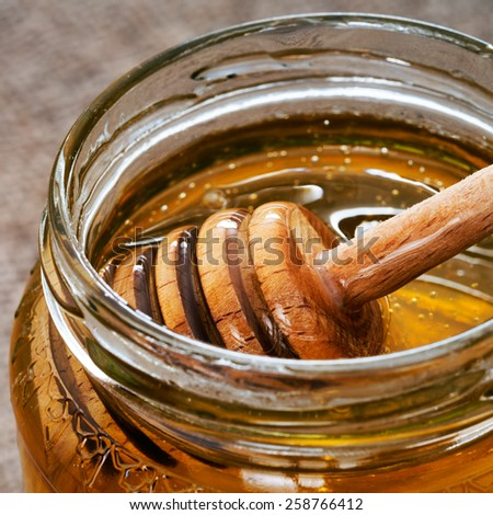 Jar of honey with dipper, detail. Closeup macro. - stock photo