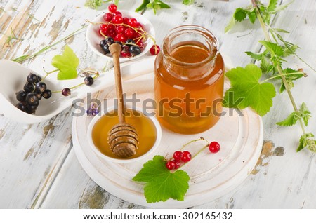 Jar of Honey with Honey Dipper and currants. Selective focus