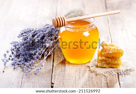jar of honey with honeycomb and lavander flowers on wooden table