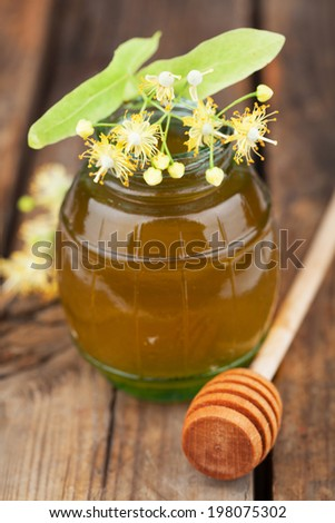 Jar of honey with linden flowers - stock photo