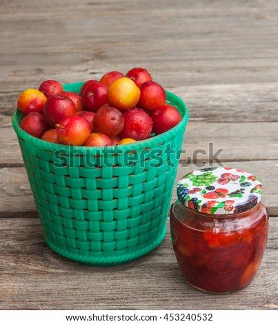 Jar of jam and a green basket with red  plums on wooden background - stock photo