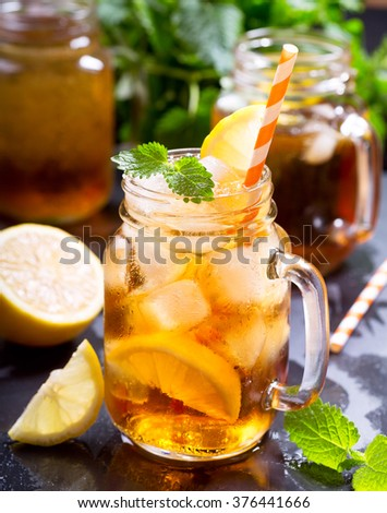 jar of lemon ice tea with striped straw - stock photo