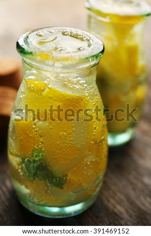 Jar of lemonade with lemon on wooden table background, closeup