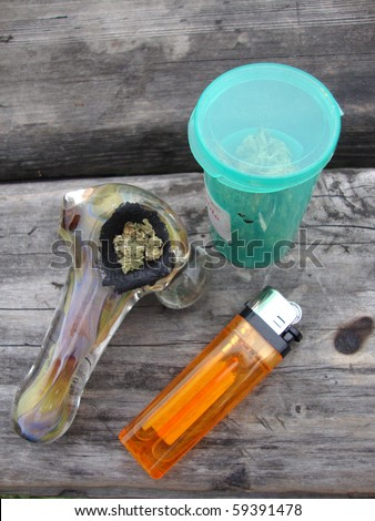 Jar of Medical Marijuana, Pipe and lighter sitting on a well used unpainted wood table in a park - stock photo