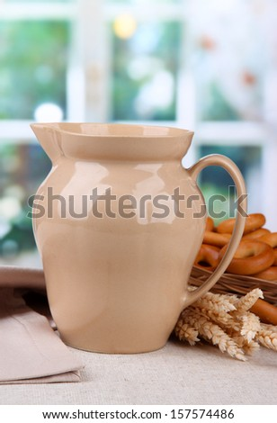 jar of milk, tasty bagels and spikelets on table - stock photo