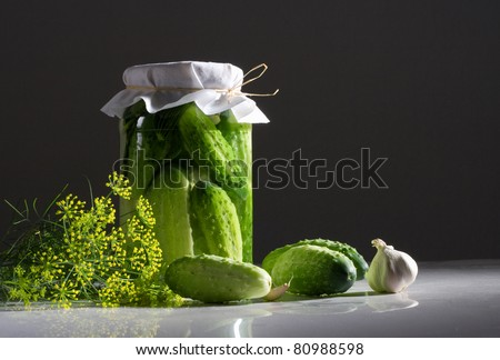 Jar of pickled cucumbers with dill and garlic on a dark background. - stock photo
