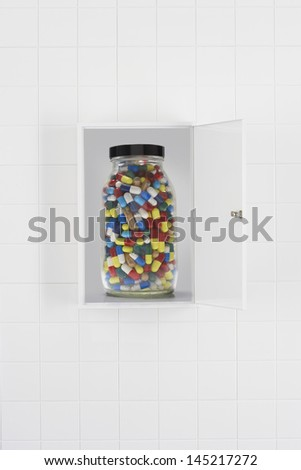 Jar of pills in bathroom cabinet - stock photo