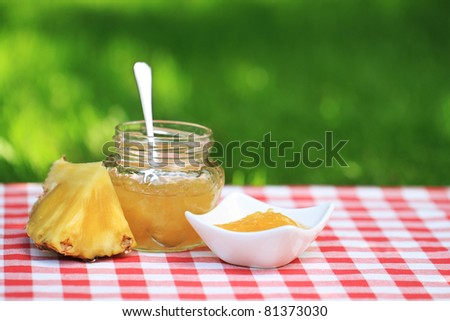 Jar of pineapple jam on the table in the summer garden