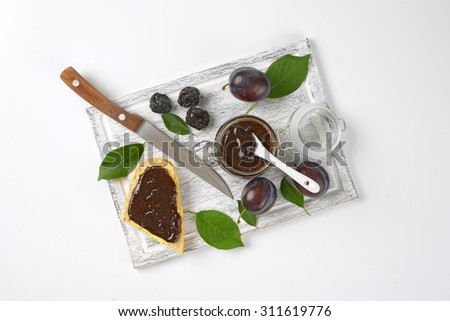 jar of plum jam, fresh and dried plums and slice of baguette on wooden cutting board - stock photo