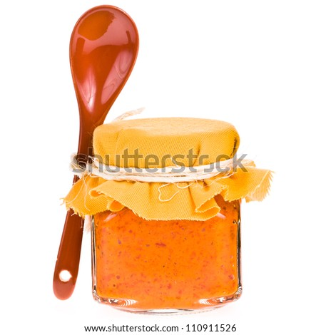 Jar of sauce from the pepper and  ceramic spoon isolated on white background - stock photo