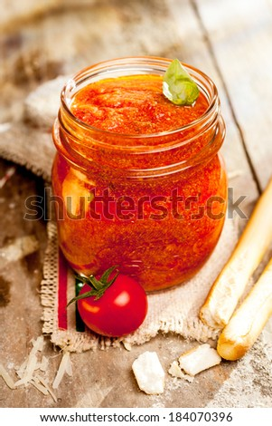 Jar of savory relish or dip with italian grissini or breadsticks on a cloth with the Italian national colors and fresh tomato - stock photo